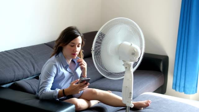 vidéos et rushes de la vidéo est sur une jeune femme rafraîchissante devant le ventilateur - canicule