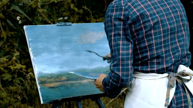 utsikten från baksidan av målaren måla ett landskap med oljefärger. 4k (4k) - människorygg bildbanksvideor och videomaterial från bakom kulisserna
