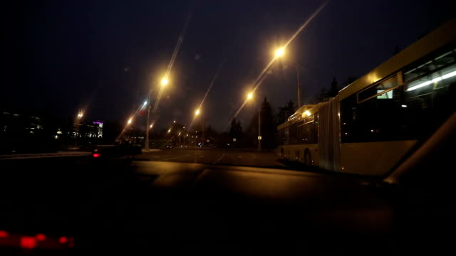 The view from the frontal window. Night city. The car outstrips big yellow bus. video
