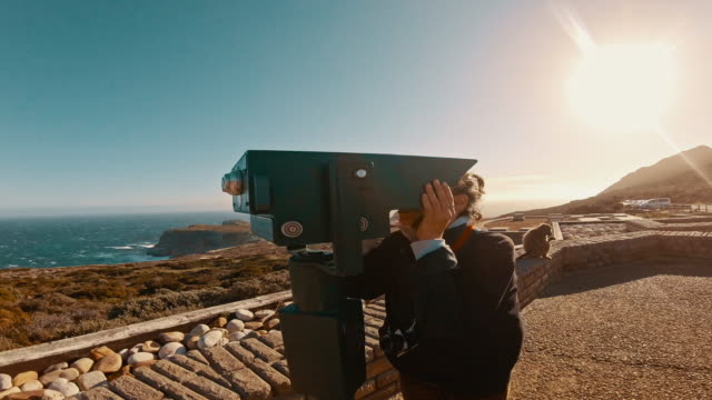 The view is simply too pretty 4k video footage of an attractive young woman using binoculars to look at the view at the Cape Point during the day western cape province stock videos & royalty-free footage