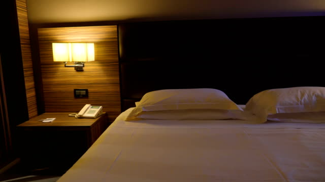 The view of the white sheet of the bed The view of the white sheet of the bed and the black headboard with the two lampshades on the side inside the room in Italy lamp shade stock videos & royalty-free footage