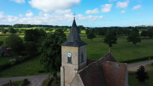 The village of Cuncy-les-Varzy in the middle of the countryside and the bell tower of St. Martin's Church at its entrance