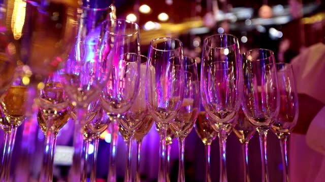 vidéos et rushes de le garçon verse le champagne dans des verres, verres à champagne sur la table dans le restaurant, les verres de champagne sur la table de fête, propres verres sur une table préparée par le barman pour le champagne - banquet