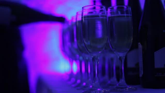 vidéos et rushes de le serveur verse du champagne dans des verres à la célébration. fête des lumières de couleur. - flûte à champagne