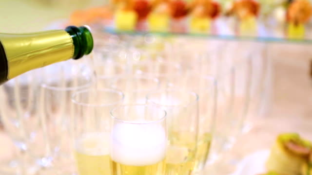 vídeos de stock e filmes b-roll de the waiter pours champagne into glasses, buffet table with plates and utensils. catering, on-site restaurant - sideboard