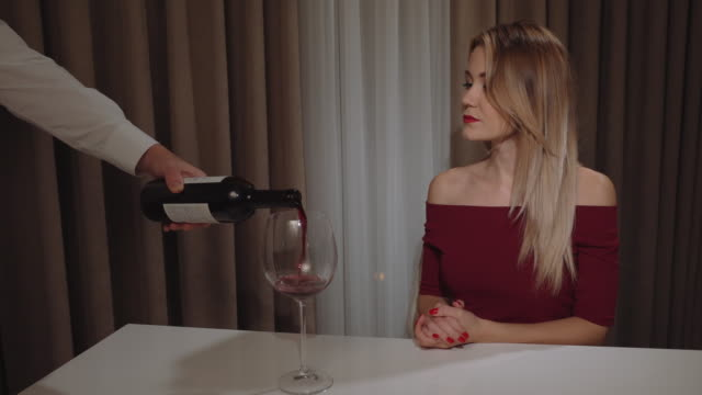 the waiter pours red wine for a beautiful young woman with red lipstick in a restaurant video