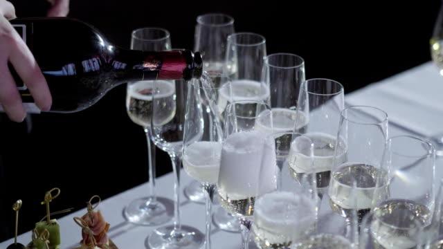 die kellner gießt den champagner in die gläser. tabelle oben voller gläser sekt mit flaschen im hintergrund. - champagner toasts stock-videos und b-roll-filmmaterial