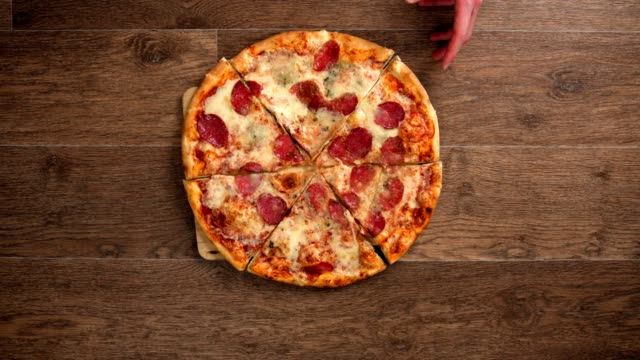 the waiter puts a board with pizza on a table, peoples hands take pieces, stop motion animation - pizza filmów i materiałów b-roll