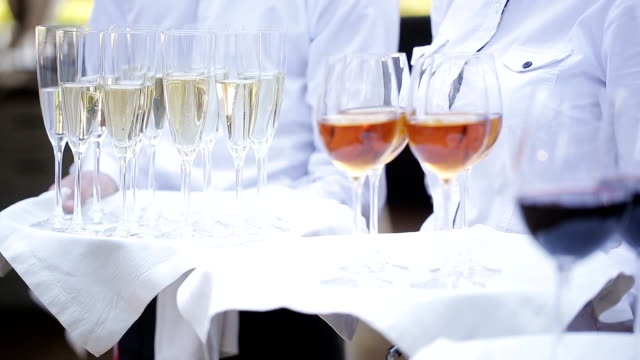 the waiters greet guests with alcoholic drinks. champagne, red wine, white wine on trays. - taca filmów i materiałów b-roll