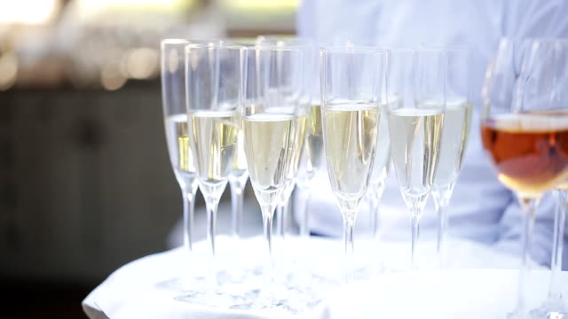 The waiters greet guests with alcoholic drinks. Champagne, red wine, white wine on trays. video