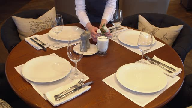 The waitress serves the table in the restaurant