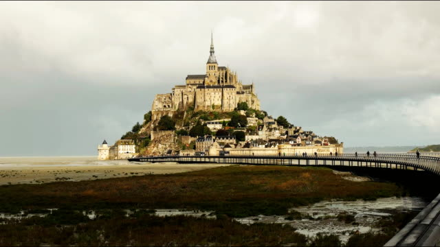the walkway to mont st michel island, normandy view of the walkway to mont st michel island in normandy france normandy stock videos & royalty-free footage