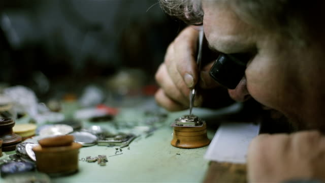 The watchmaker is repairing and maintaining an automatic mechanical watch - fixing and examining pendulum