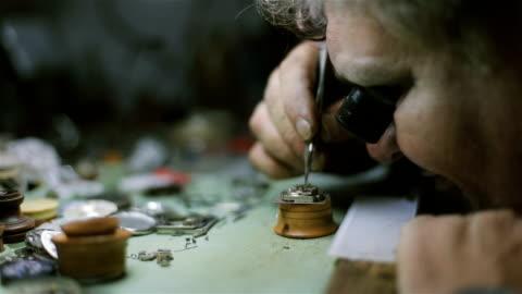 vidéos et rushes de l'horloger est réparer et entretenir une montre mécanique automatique - fixation et examinant la pendule - exactitude