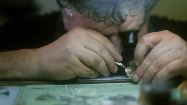 die uhrmacher ist reparatur und wartung von uhren - antique shop stock-videos und b-roll-filmmaterial