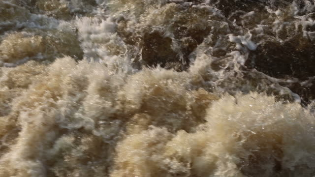 the water flowed rapidly, boiling, splattered, and furiously. - furioso video stock e b–roll