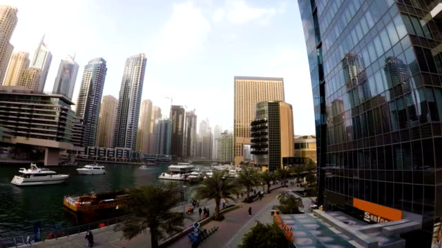 The waterfront Dubai Marina with a promenade where walking tourists and marine canal where sailing boats video