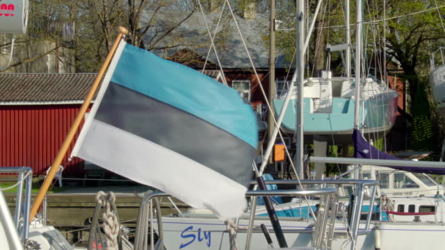 The waving Estonia flag on the small pole on the sailboat video