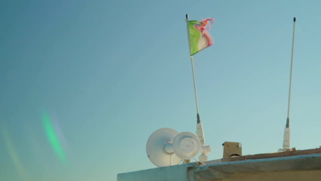 The waving small flag of Italy on the edge of the white boat video