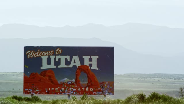 """the """"welcome to utah"""" on the utah/colorado border (eastern utah) on interstate 70 with mountains in the background - stan utah filmów i materiałów b-roll"""