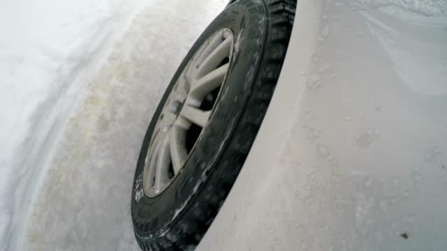 la ruota dell'auto sulla strada innevata - slitta video stock e b–roll