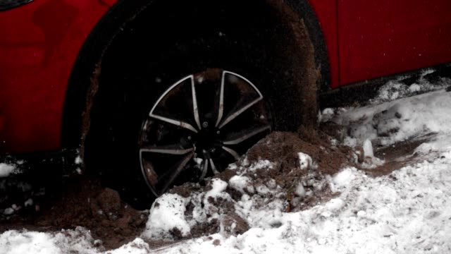 The wheel of the car slides on the snow and the ground, can not leave The wheel of car slides on the snow and the ground, can not leave. Red car on snow-covered road. Wheel slides on the snow, stuck in a snowdrift, closeup view. Wheel rotates in the snow in slow motion. towing stock videos & royalty-free footage