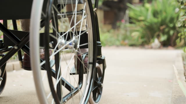 The wheels keep turning 4k video shot of an unrecognizable elderly person being pushed in a wheelchair by a nurse outside of an old age home during the day orthopedic equipment stock videos & royalty-free footage