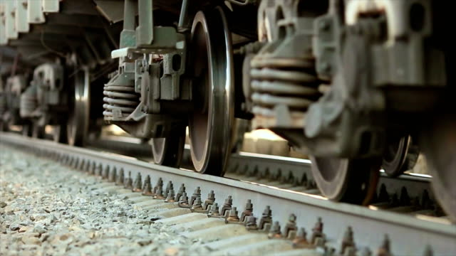 The wheels of old train on the railway track passing by camera. Close up shot.
