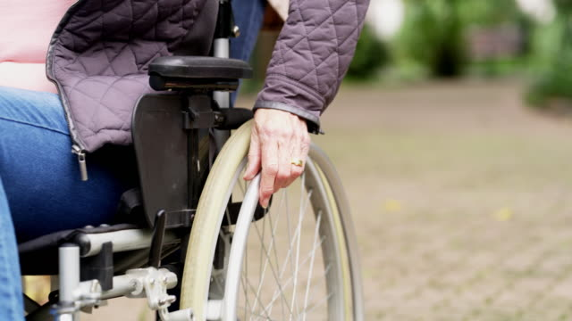 The wheels to take her wherever she needs to go 4k video footage of a senior woman pushing her wheelchair through the park wheelchair stock videos & royalty-free footage