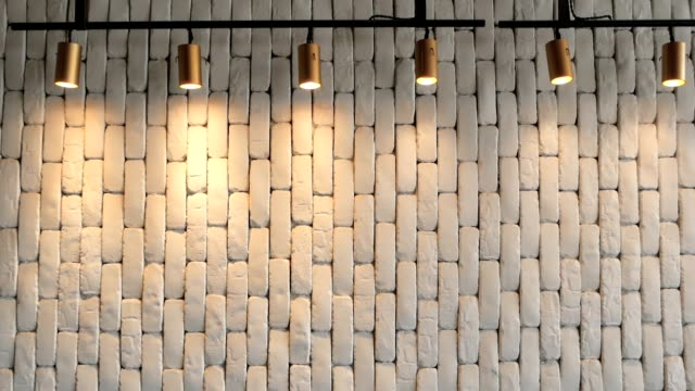 The white brick wall is hilighted with lanterns from above. Background texture video