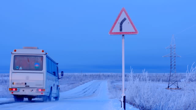 The white bus is moving along a snowy country road that goes to the right, as the road sign says