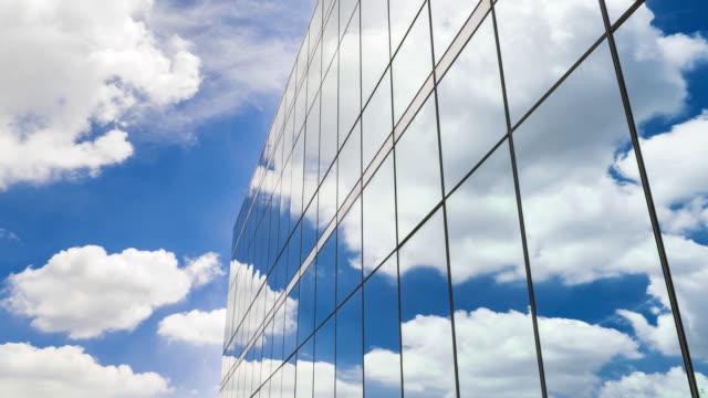 the white clouds are reflected in the windows of the building - odbicie zjawisko świetlne filmów i materiałów b-roll