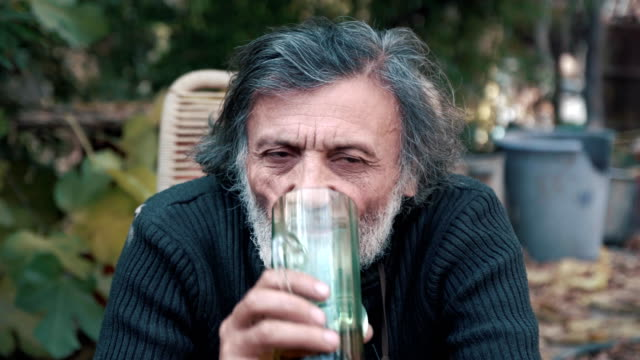 vídeos de stock e filmes b-roll de the white-haired man drinking beer and intently look at the camera - reis magos
