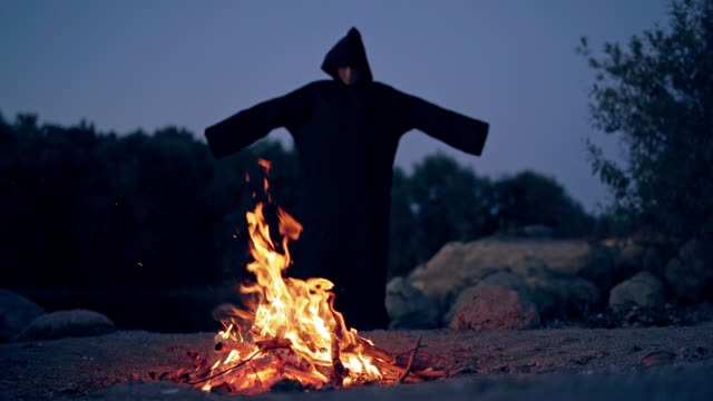 The wicked witch performs a ritual near a bonfire in the night. The wicked witch performs a ritual near a bonfire in the night. Mysticism of Halloween bonfire stock videos & royalty-free footage