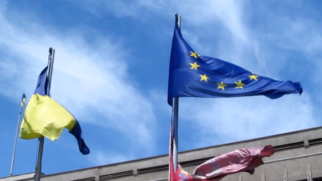 the wind develops flags of ukraine and the european union in the blue sky - 34s - passports and visas stock videos and b-roll footage