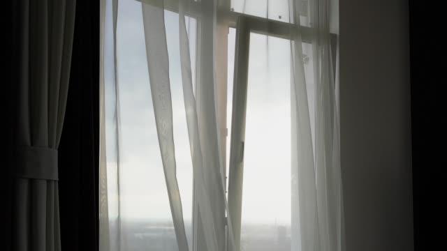vidéos et rushes de le vent de la fenêtre secoue les rideaux - rideaux