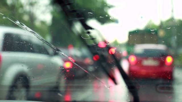 vídeos de stock, filmes e b-roll de o limpador de para-brisas remove gotas de chuva no para-brisa - tráfego