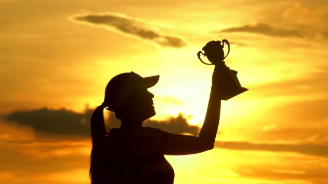 vídeos de stock, filmes e b-roll de o vencedor segurando um troféu na silhueta do pôr do sol - troféu