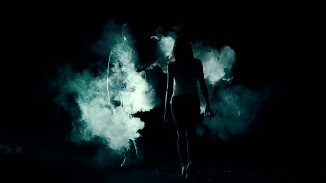 The woman and man walking through the smoke cloud in the dark background