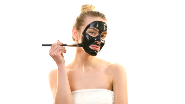 the woman applying a black face mask on the white background - facial stock videos & royalty-free footage
