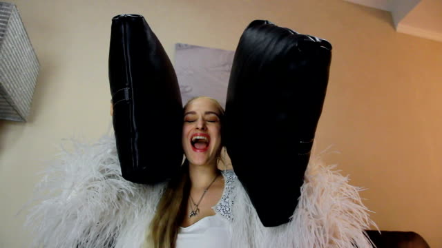 vídeos y material grabado en eventos de stock de la mujer cubrió sus oídos con almohadillas y abrió su boca - almohada