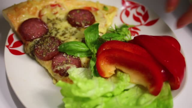 The woman decorates with appetizing greens cooked pizza. video