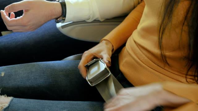 vídeos de stock, filmes e b-roll de a mulher fixá-lo com um cinto de segurança a bordo do avião - plano médio