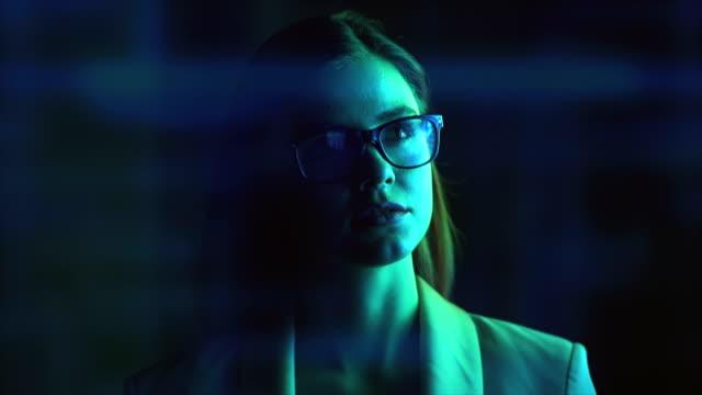 那個戴眼鏡的女人走在一個靠近展覽的黑暗房間裡。慢動作 - 投射 個影片檔及 b 捲影像