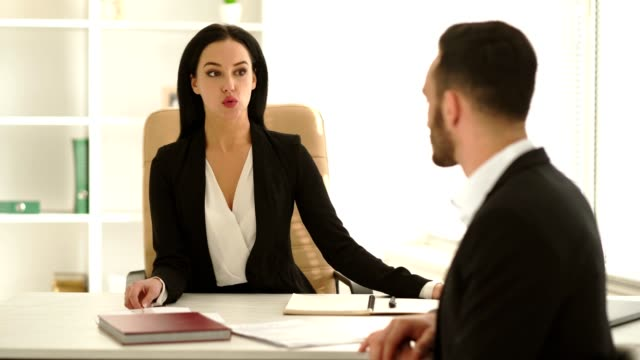 The woman interviews a man at the office table