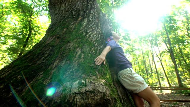 The woman leaned back against a big beautiful oak