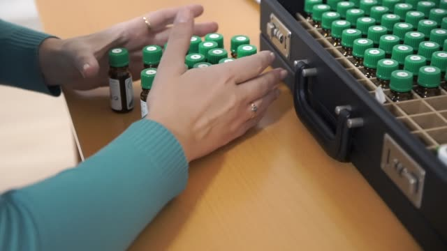 The woman moves the medical bottles and shifts them out of the case. Recalculates the cosmetic mixture video
