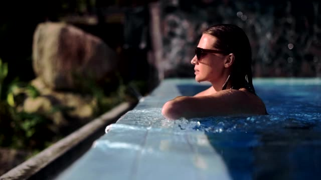 The woman on the edge of the pool looks into the distance. The woman on the edge of the pool looks into the distance. spa stock videos & royalty-free footage