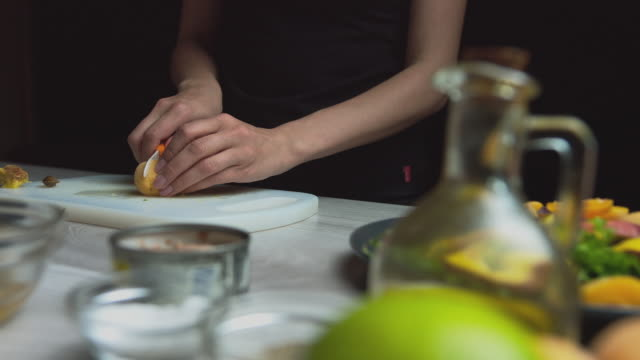 The woman prepares the sauce for the salad, adds oil to the sauce. On a dark background. Food at home
