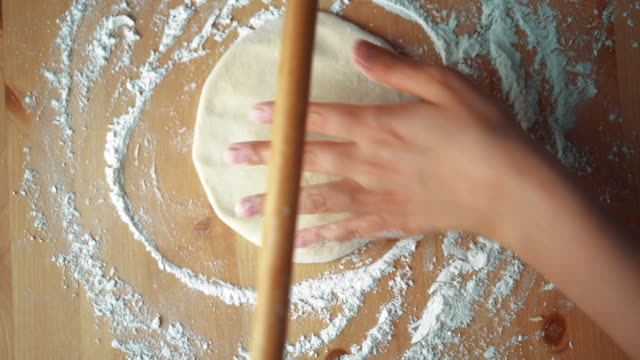 The Woman Preparing Turkish Traditional Food Mantı (Turkish Ravioli) Manti (Mantı) is Turkish traditional food like Italian ravioli, especially Kayseri Mantısı. Roll out the dough with rolling pin. ravioli stock videos & royalty-free footage
